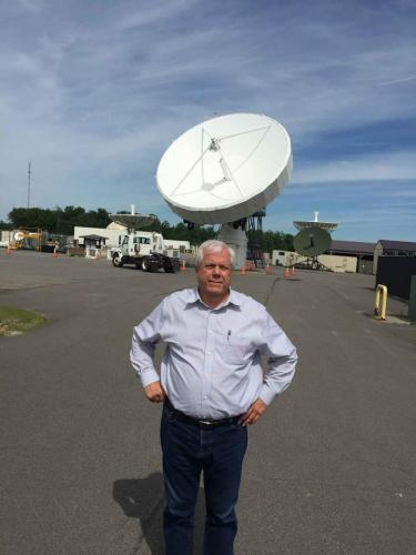 Pat Morgan next to a satellite dish